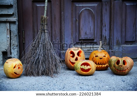 Pumpkin and broom for holiday Halloween on old wooden door background - stock photo