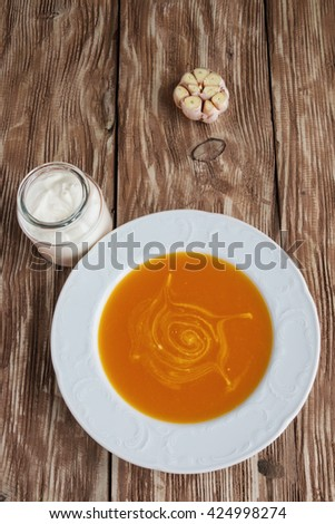 Pumpkin and carrot creamy soup in a white plate, garlic and sour cream on old wooden background. Top view.