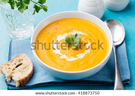 Pumpkin and carrot soup with cream and parsley on blue stone background  - stock photo
