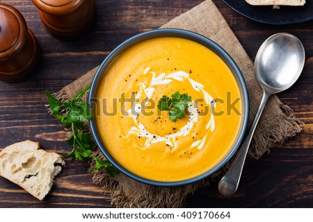 Pumpkin and carrot soup with cream and parsley on dark wooden background Top view - stock photo
