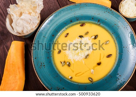 Pumpkin and carrot soup with parmesan cheese, pumpkin seeds and bread on dark wooden background. Top view