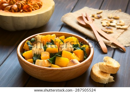 Pumpkin and chard salad with croutons served in wooden bowl, photographed on dark wood with natural light (Selective Focus, Focus in the middle of the salad)  - stock photo