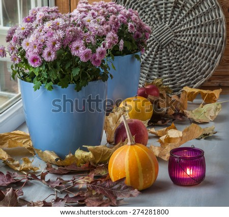 Pumpkin and chrysanthemum on the box next to  candle before the holiday - stock photo