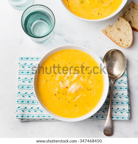 Pumpkin and coconut soup with chicken on white stone background - stock photo