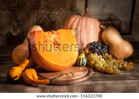 Pumpkin and gourds, grapes on a rustic wooden table
