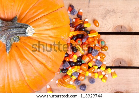 Pumpkin and halloween candy on a wooden crate in background - stock photo