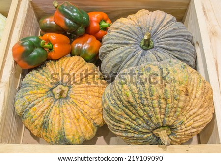pumpkin and pepper harvested products on wooden box.