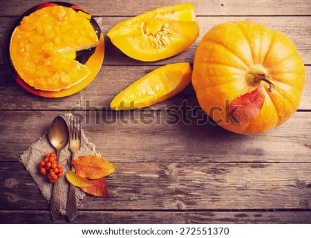 pumpkin and pie on wooden table - stock photo