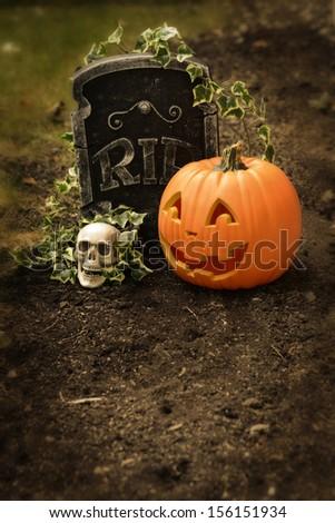 pumpkin and skull at grave - stock photo