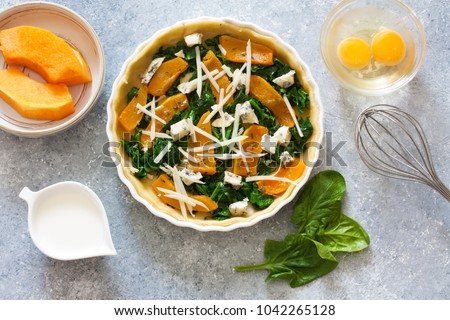 Pumpkin and spinach pie ( quiche) and ingredients above eggs, cream, leaves of spinach, slices of pumpkin over white wood background. Top view