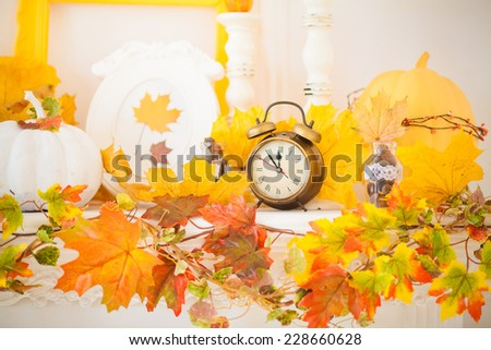 pumpkin and the clock on the fireplace - stock photo