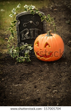 Pumpkin and tombstone - stock photo