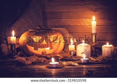 Pumpkin around burning candles - stock photo