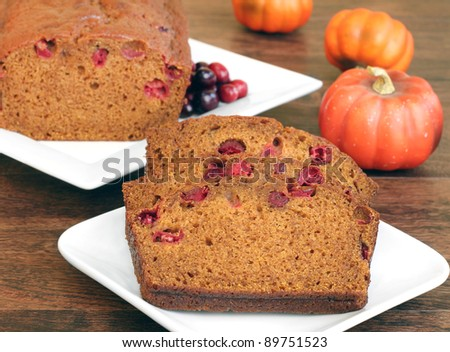 Pumpkin cranberry bread, both whole and sliced in a fall setting.  Selective focus on front slice. - stock photo