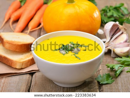 Pumpkin cream soup, fresh vegetables and toast bread on wooden table - stock photo
