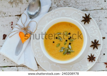 Pumpkin cream soup in a bowl  on a vintage plate with seeds and spices - stock photo