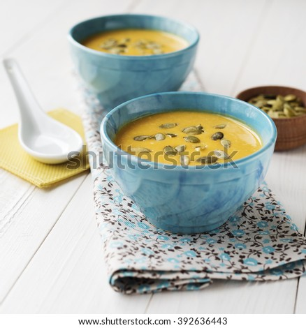 Pumpkin cream-soup on a wood background