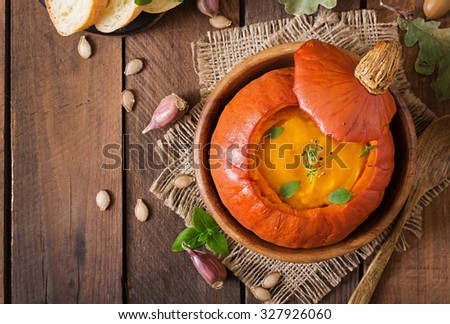 Pumpkin cream soup with peppers and herbs in a pumpkin. Top view - stock photo