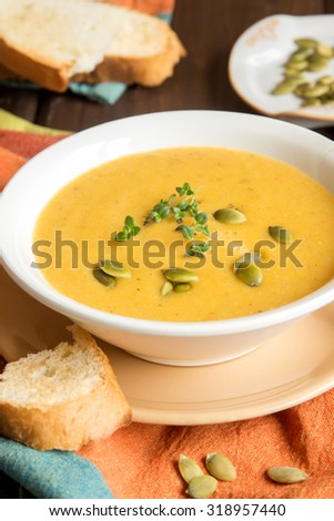 Pumpkin cream soup with pumpkin seeds and herbs in bowl on rustic wooden table