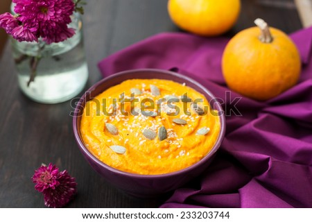 Pumpkin cream-soup with seeds in violet bowl - stock photo