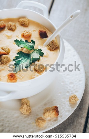Pumpkin creamy soup with parsley on wooden background