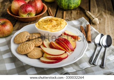 Pumpkin dip with cinnamon, homemade biscuits and a delicious apple slices - stock photo