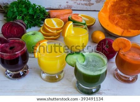 Pumpkin fresh juice, beet juice, cucumber juice. Orange fresh juice. Vegetables and fruit on the table - stock photo
