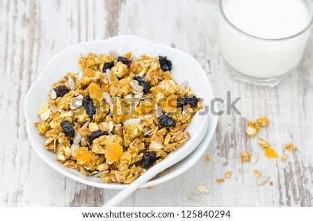 pumpkin granola with dried fruit and seeds in a white bowl, top view - stock photo
