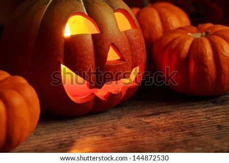 Pumpkin head and small pumpkins in dark with copy space. - stock photo