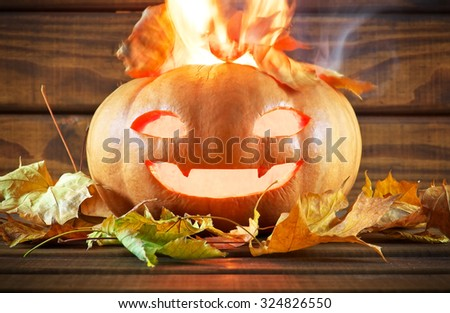 Pumpkin head on wooden background. Fire in pumpkin. - stock photo