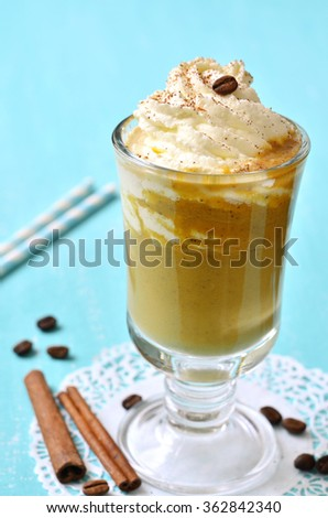 Pumpkin latte with cinnamon,caramel and whipped cream on turquoise background. - stock photo