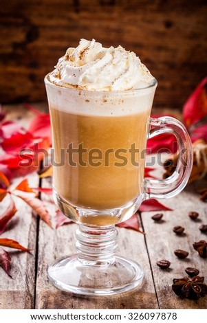 pumpkin latte with whipped cream in a glass jar on a rustic background - stock photo