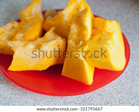 pumpkin on red plate in a kitchen on a table