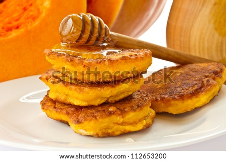 pumpkin pancakes with honey on a background of ripe pumpkins