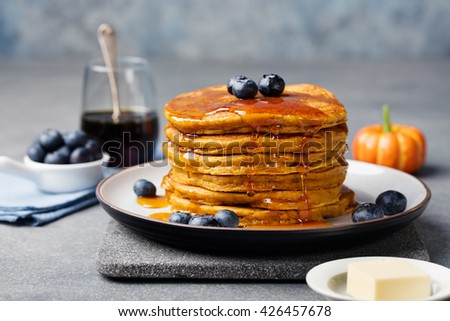 Pumpkin pancakes with maple syrup and blueberries on a plate. Grey stone background - stock photo