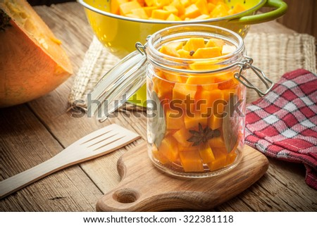 Pumpkin pickle in a glass container on a wooden table. - stock photo