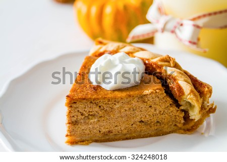 Pumpkin pie and decorations, white wood background, closeup