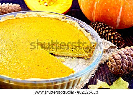 Pumpkin pie in a glass pan on sackcloth, gourd, pine cones and maple leaf on the background of dark wood planks - stock photo
