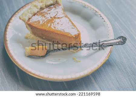 Pumpkin pie on a white china plate with gold detailed rim and antique silver dessert fork. - stock photo