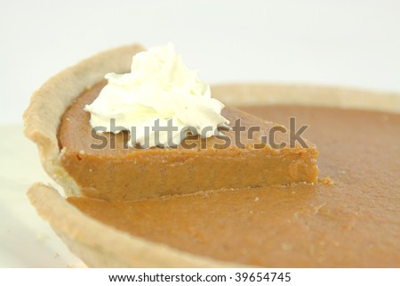 Pumpkin pie piece decorated with whipped cream over. Blurred.