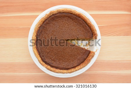 Pumpkin pie served for Thanksgiving with one slice taken  - stock photo