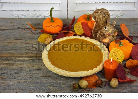 pumpkin pie with fall leaves and candle on rustic barn wood