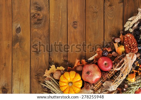 pumpkin, pomegranate, apple, nuts, berries and grain on old weathered wooden floor - stock photo