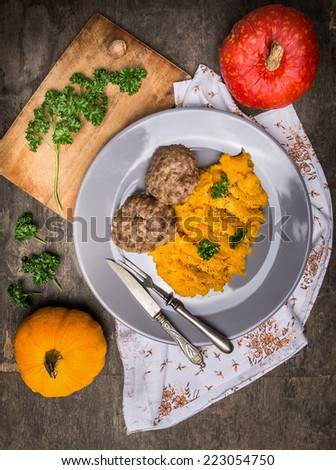 Pumpkin puree with meat patties in plate  on old wooden table, top view - stock photo