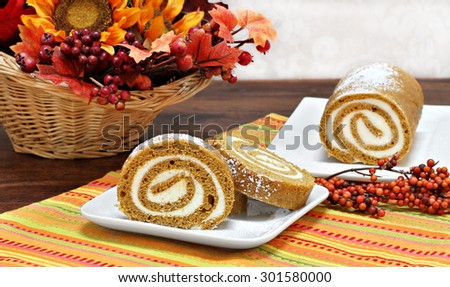 Pumpkin roll cake, whole and sliced, in a fall setting.