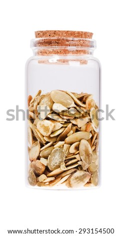 Pumpkin seeds in a glass bottle with cork stopper, isolated on white. - stock photo