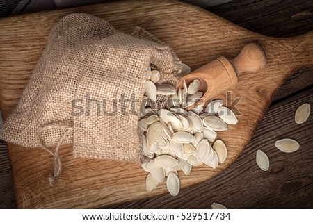 Pumpkin seeds in a sack and spoon on the wooden table.  Dark light.