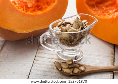 Pumpkin seeds in bowl on white wooden table. Selective focus. - stock photo