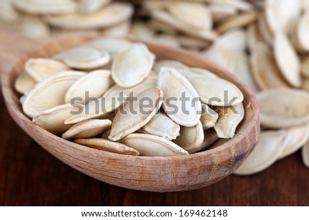 Pumpkin seeds in spoon on table close up