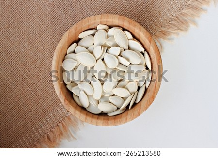 Pumpkin seeds in wooden bowl - stock photo
